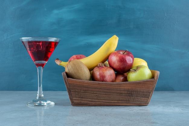 Smaczny sok z kostkami lodu i różnymi owocami.
