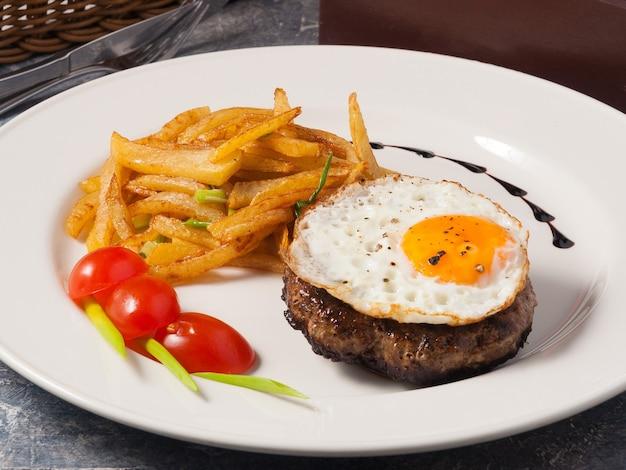 Smaczny stek z jajkiem i ziemniakami w domu na białym talerzu