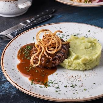 Smaczny stroganow wołowy z puree ziemniaczanym i solonym ogórkiem