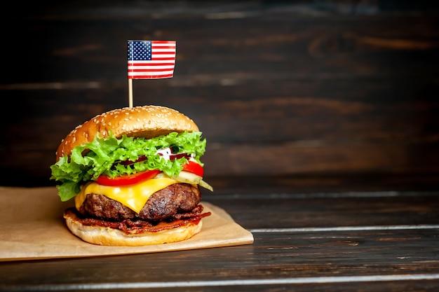 Smaczny świeży domowy burger z amerykańską flagą na drewnianym stole