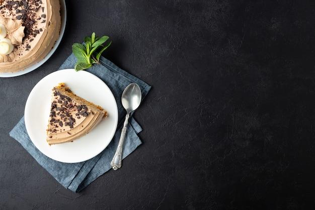 Smaczny tort ozdobiony kremem i ciemną czekoladą na czarnym tle. widok z góry z miejsca na kopię.