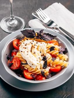 Smaczny włoski makaron fusilli z wiśniami, mozzarellą lub buratta i świeżą bazylią. danie z makaronem na ciemnym blacie. skopiuj miejsce.
