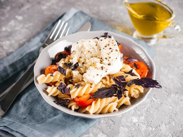 Smaczny włoski makaron fusilli z wiśniami, mozzarellą lub buratta i świeżą bazylią. danie z makaronem na szarym tle betonu.