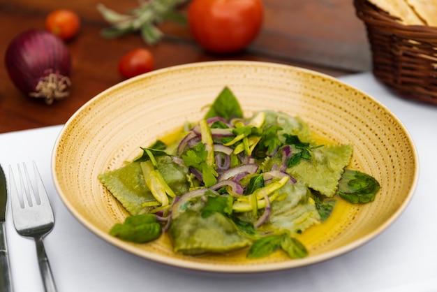 Smaczny zielony makaron ravioli z cebulą i liśćmi bazylii w ceramicznym talerzu