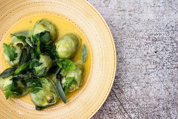 Smaczny zielony makaron ravioli z kolendrą i liściem bazylii w talerzu
