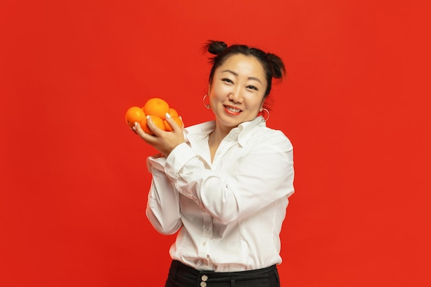 Smak wakacji. szczęśliwego chińskiego nowego roku 2020. azjatycka młoda kobieta trzyma mandarynki na czerwonym tle w tradycyjnej odzieży.