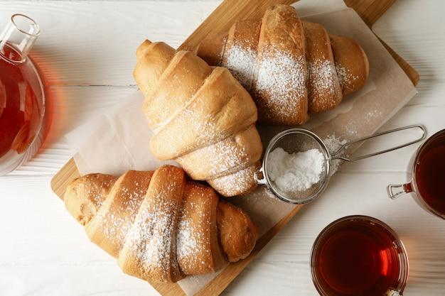 Smakowici croissants i filiżanki z herbatą na drewnianym tle, odgórny widok