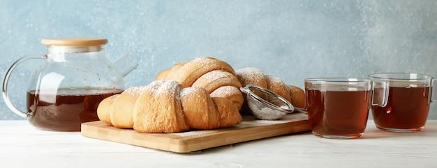 Smakowici croissants i filiżanki z herbatą na drewnianym tle, przestrzeń dla teksta