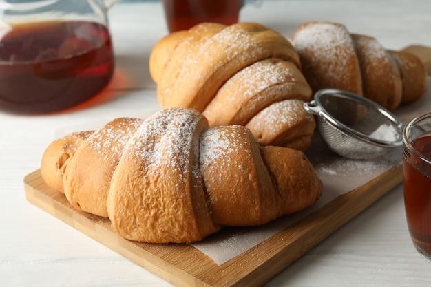 Smakowici croissants i filiżanki z herbatą na drewnianym tle, zamykają up