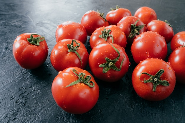 Smakowici czerwoni dojrzali świezi pomidory z wodą opuszczają na ciemnym tle. warzywa zebrane z ogrodu. domowe surowe jedzenie. z bliska strzał.