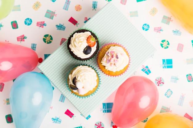 Smakowici muffins na teraźniejszości pudełku blisko jaskrawych balonów