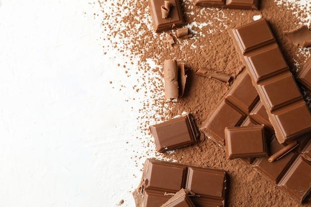 Smakowita czekolada i proszek na białym tle. słodkie jedzenie