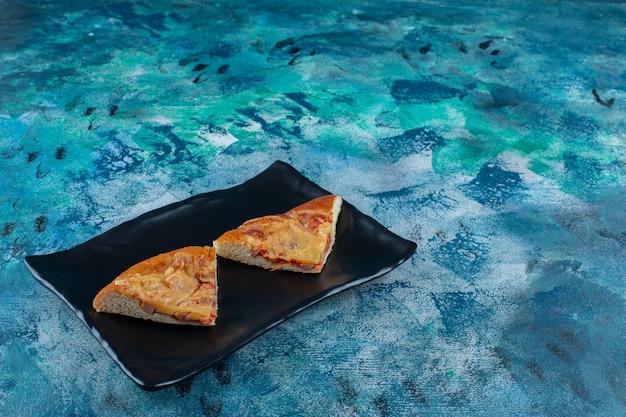 Smakowita mini pizza na czarnym talerzu, na marmurowym stole.