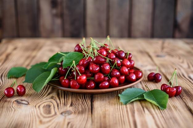 Smakowita soczysta słodka wiśnia na drewnianym tle. może być używany jako tło