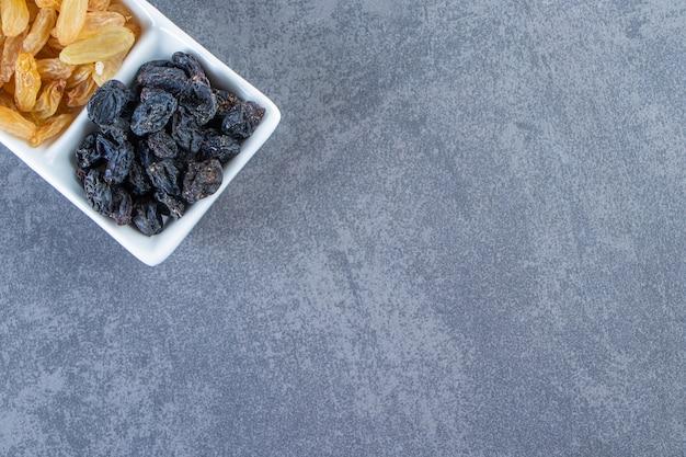 Smakowite rodzynki na talerzu, na marmurowym tle.