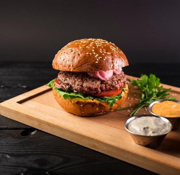 Smakowity cheeseburger na drewnianej desce przygotowywającej słuzyć