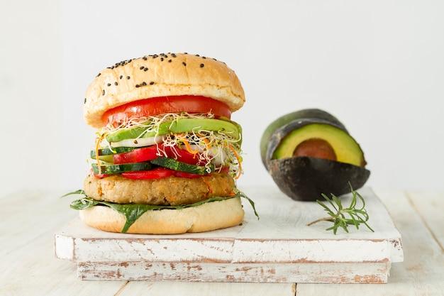 Smakowity hamburger i avocado na drewnianej desce
