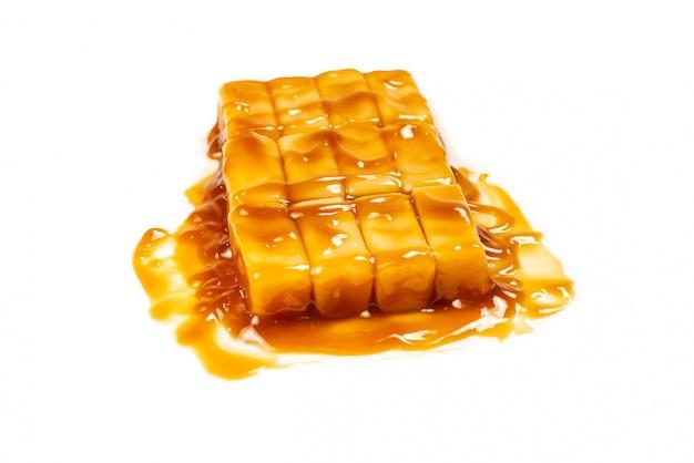 Smakowity karmelu cukierek odizolowywający na białym tle.