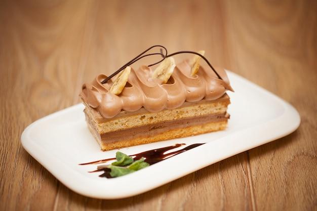 Smakowity kawałek czekoladowy tort na drewnianym stołowym tle