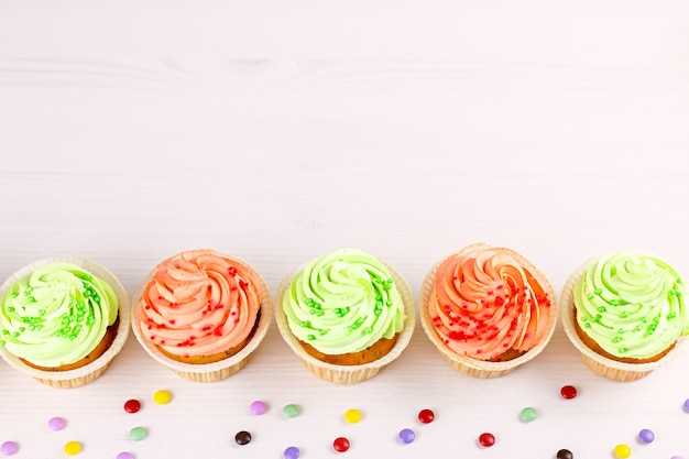 Smakowity kolorowy babeczki zbliżenie na bokeh tle z kopii przestrzenią. słodycze na przyjęcie urodzinowe