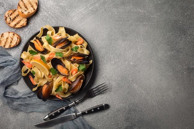 Smakowity makaron z małżami, kałamarnicą, pietruszką i cytryną, odgórny widok.