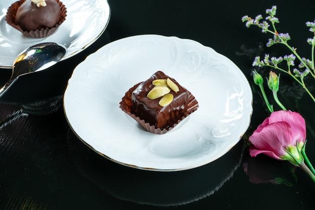 Smakowity słodki chockolate cukierek na białym spodeczku na ciemnym tle. deser herbaciany. zdjęcie jedzenia