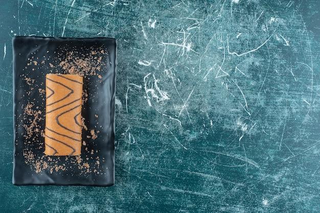Smakowity tort bułkowy na czarnym talerzu, na niebieskim tle. zdjęcie wysokiej jakości