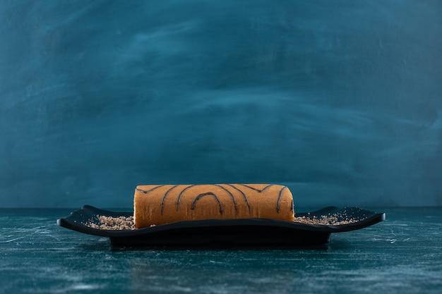 Smakowity Tort Bułkowy Na Czarnym Talerzu, Na Niebieskim Tle. Zdjęcie Wysokiej Jakości Darmowe Zdjęcia