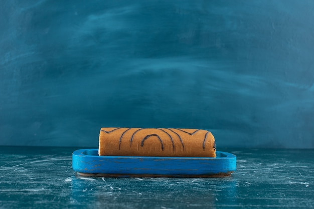 Smakowity tort rolkowy na drewnianym talerzu, na niebieskim tle. zdjęcie wysokiej jakości