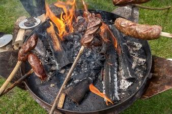 Smalec wędzony (Slanina), kiełbaski i chleb gotowane na ogniu.