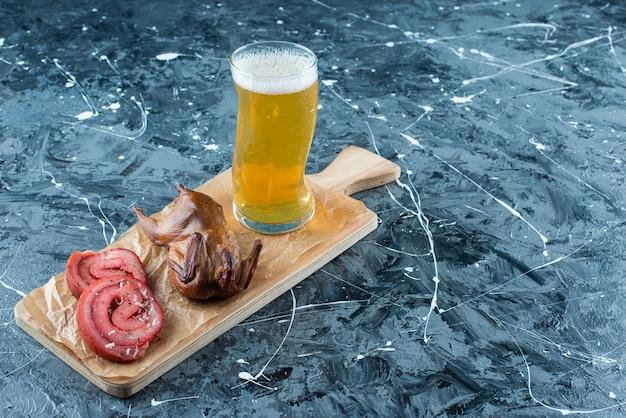 Smalec wieprzowy, grill i piwo na desce do krojenia, na niebieskim stole.