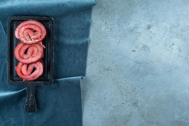 Smalec wieprzowy na desce na kawałkach materiału, na niebieskim stole.