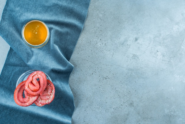 Smalec wieprzowy na szklanej misce i kufel piwa na kawałku tkaniny, na niebieskim tle.