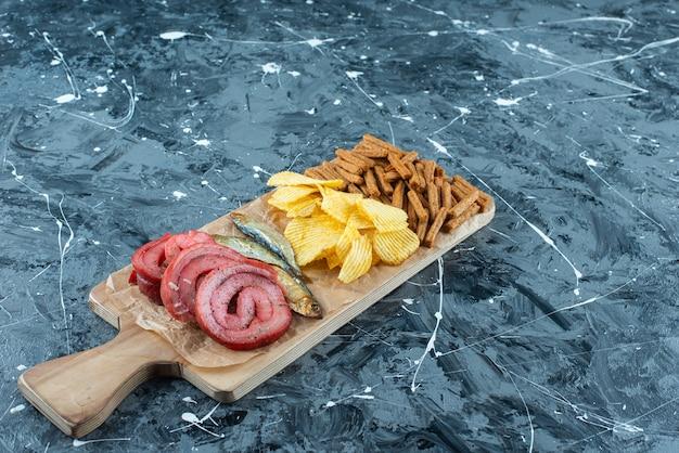 Smalec wieprzowy, ryba, frytki i bułka tarta na desce do krojenia, na niebieskim stole.