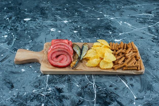 Smalec wieprzowy, ryby, frytki i bułka tarta na desce do krojenia, na niebieskim tle.