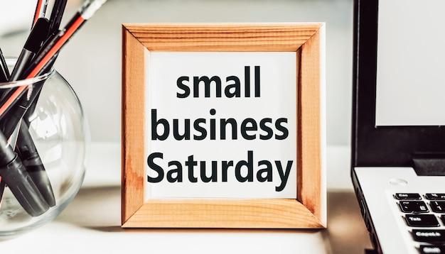 Small business saturday tekst w drewnianej ramie na stole w biurze