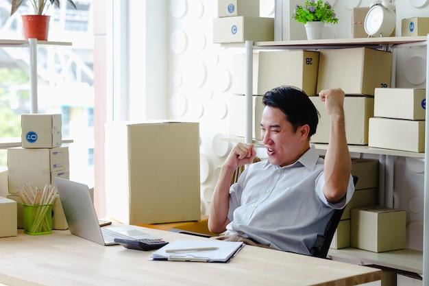 Small business sme, men bardzo szczęśliwy pracujący przyglądający rozkaz online na laptopie