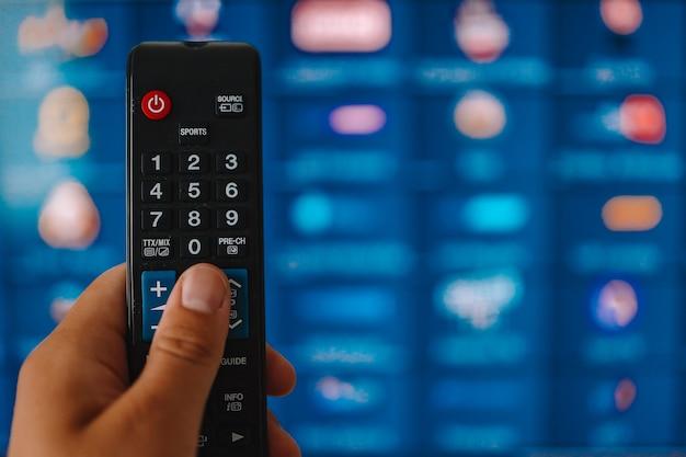 Smart tv i ręcznie naciskając pilota. dłoń trzymająca pilota do telewizora z telewizorem w tle. ścieśniać.