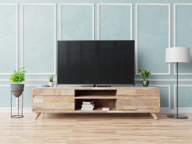 Smart tv na szafce w nowoczesnym salonie na tle niebieskiej ściany
