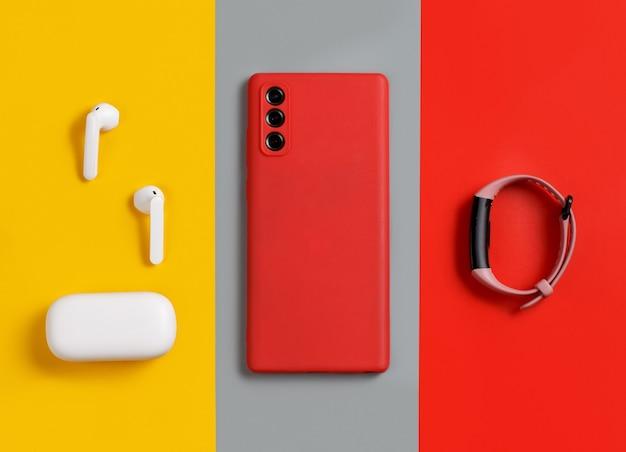 Smartfon, białe słuchawki bezprzewodowe z etui i widokiem z góry na inteligentny zegarek na czerwonym, szarym i żółtym tle