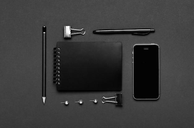 Smartfon, długopis, ołówek, artykuły papiernicze na ciemnoszarym tle
