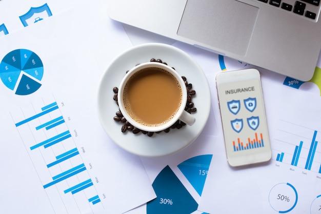 Smartfon do wyszukiwania ubezpieczenia online i kawy, dokumentu, laptopa na biurku rano. pojęcie ubezpieczenia