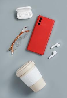 Smartfon, filiżanka kawy wielokrotnego użytku, bezprzewodowe słuchawki i okulary na szarym tle widok z góry