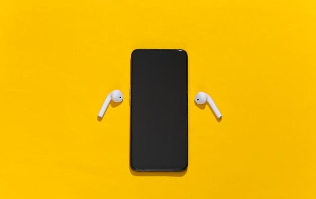 Smartfon i białe prawdziwe bezprzewodowe słuchawki bluetooth lub wkładki douszne na jasnożółtym tle.