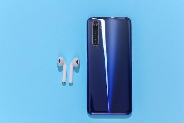 Smartfon i białe, prawdziwe bezprzewodowe słuchawki bluetooth lub wkładki douszne