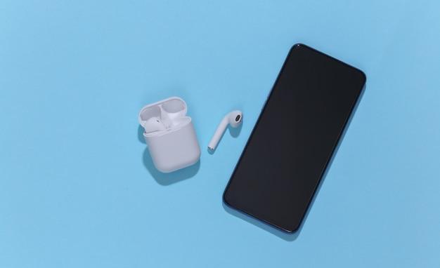 Smartfon i białe prawdziwie bezprzewodowe słuchawki bluetooth lub wkładki douszne w etui ładującym