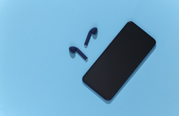 Smartfon i klasyczne, niebieskie, bezprzewodowe słuchawki lub wkładki douszne bluetooth
