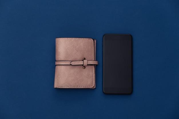 Smartfon i portfel na klasycznym niebieskim tle. kolor 2020. widok z góry.