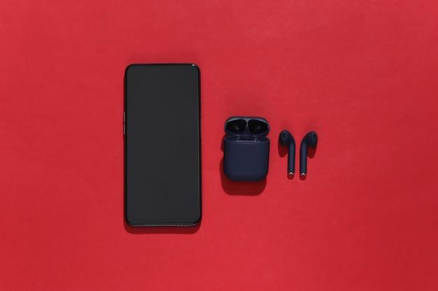 Smartfon i prawdziwe bezprzewodowe słuchawki bluetooth lub wkładki douszne z etui ładującym