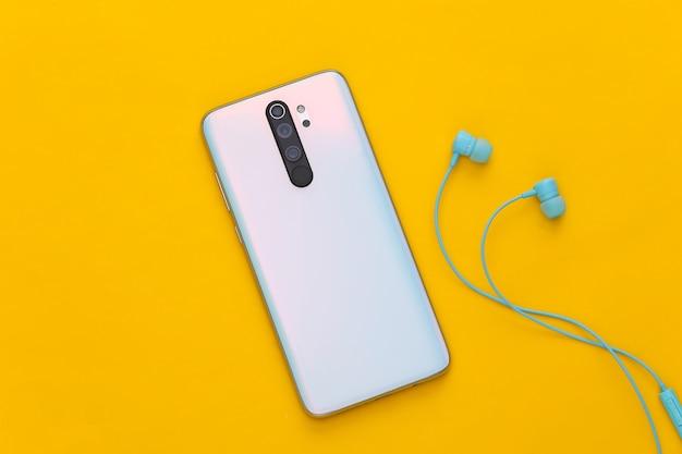 Smartfon i słuchawki na żółto